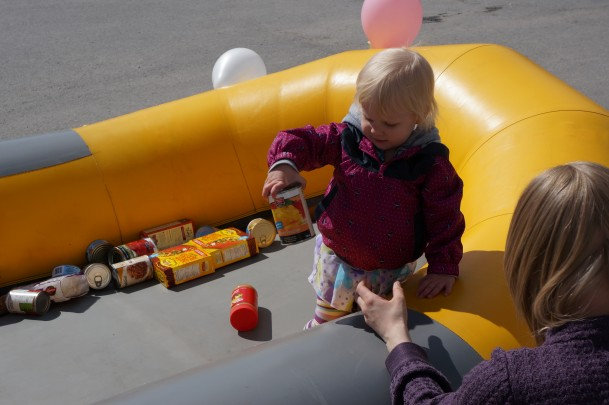 A little girl giving a food donation to our Fill a Raft Campaign