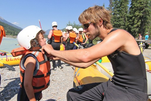 A Glacier guide fixing a young rafters helmet in Golden BC