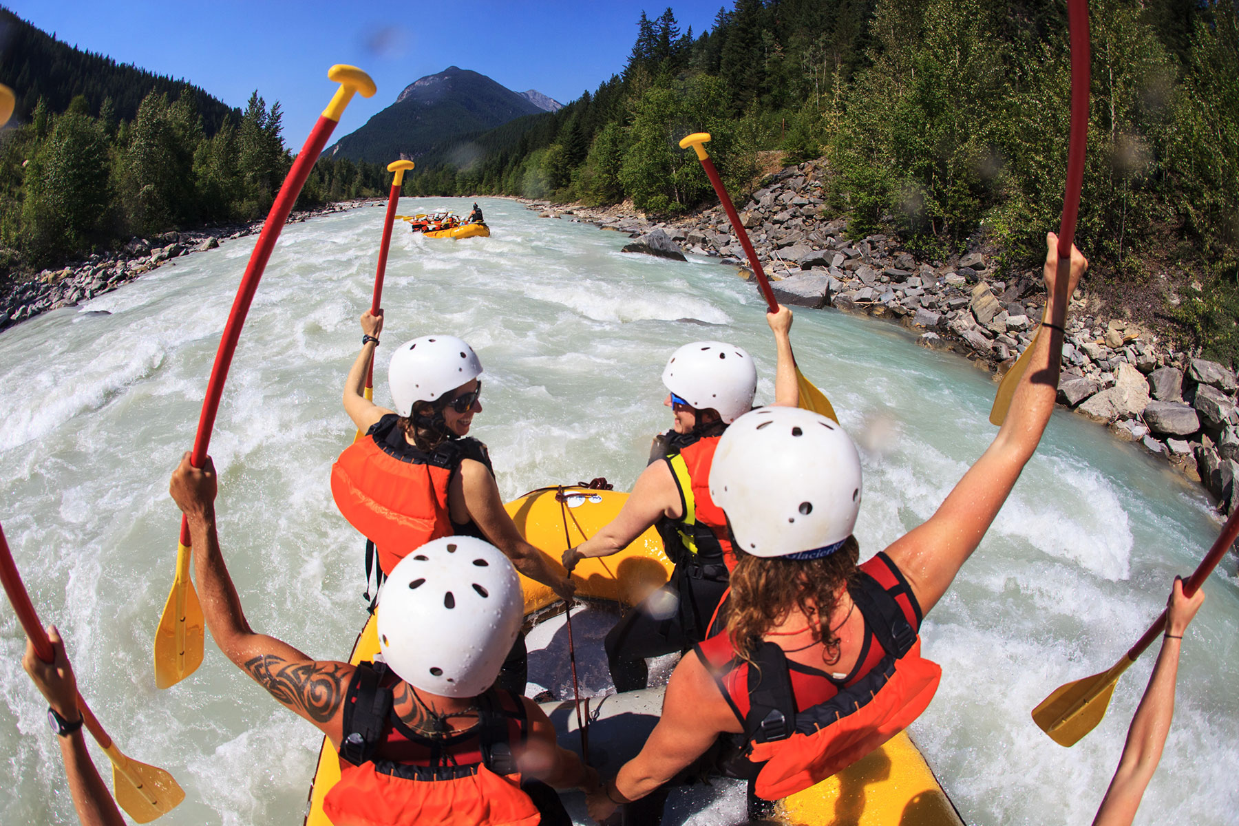 Rafters standing up to go through some rapids while white water rafting the Kicking Horse River.