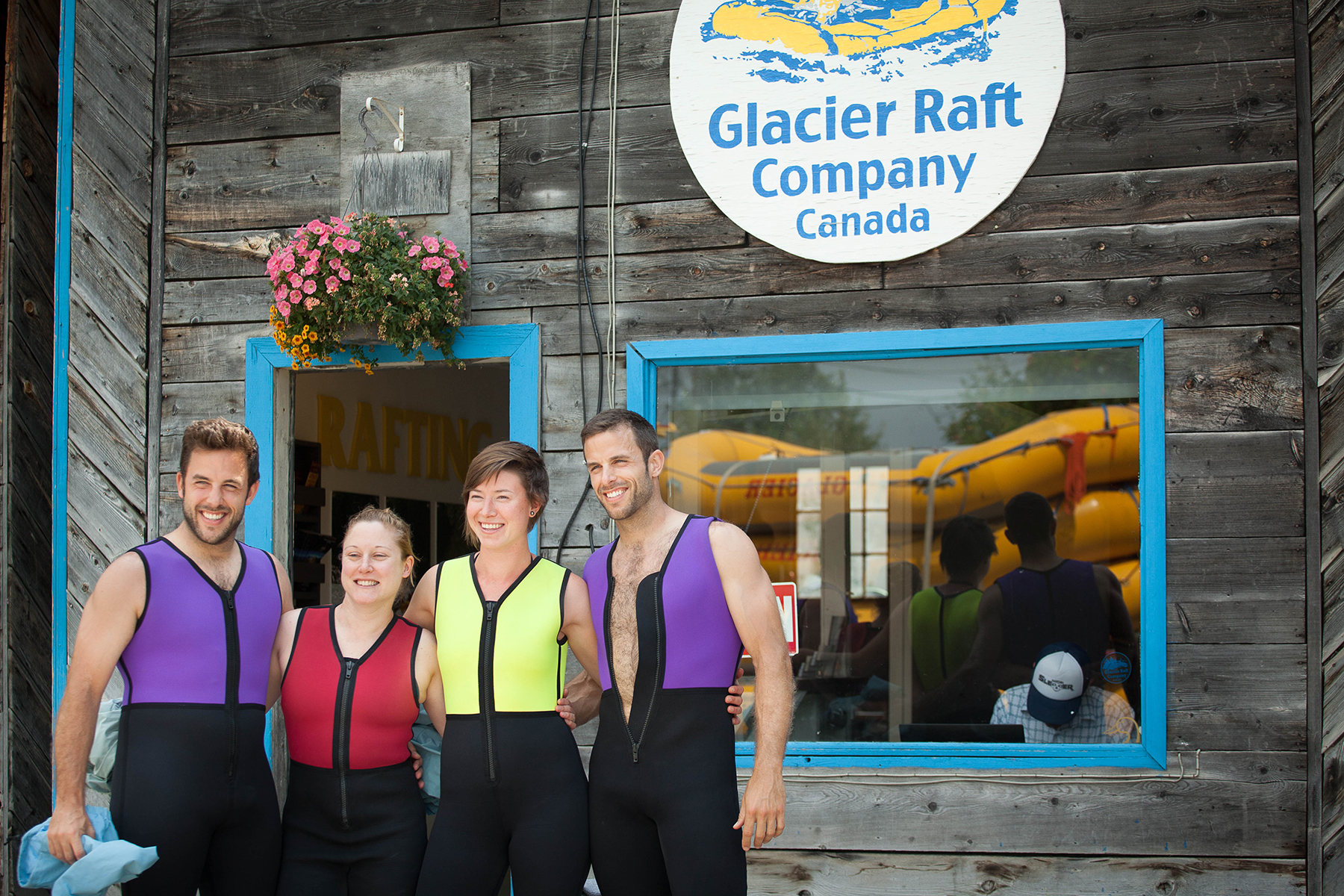 Four guests posing for a photo in front of the Glacier Raft Company base