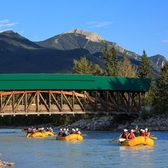 End of day light, timber frame bridge with the Rocky Mountains behind.